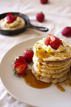 A stack of pancakes with strawberries and whipped cream on top with another small black pan of a pancake in the background